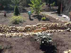 A sample of how Anne has taken rocks from the soil, created a dry river bed and incorporated art from a local artist